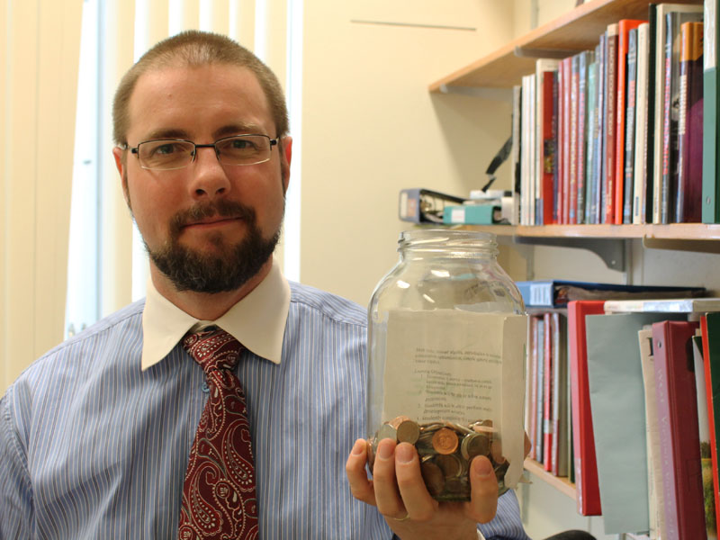 Jason Childs, an economics professor at U of R, counts the last of his pennies before they are taken out of circulation. Photo by Shinoah Young