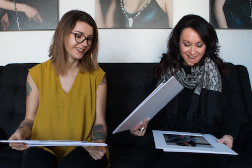 Photographer Jackie Larkin (left) shows her client, Veronica Wilgosh (right) the final prints from their recent boudoir shoot in Larkin's studio in Regina on Feb. 8, 2017. Photo by Caitlin Taylor.