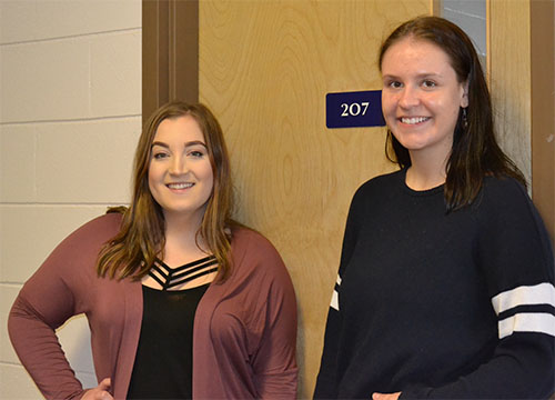 Shanae Fyke (left) and Jenessa Greer (right) pose in front of room 207 in Luther College, where they met in a Women and Gender Studies class. Photo by Jayda Noyes.