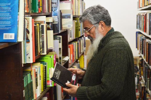 Stewart Klyne looks through his inventory at SK Books & Collectibles on 919C Albert St. Photo by Ethan Stein.