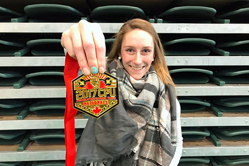 Regina athlete Anna Schneider holds up her gold medal from the 2017 CPU Powerlifting and Bench Press Nationals.